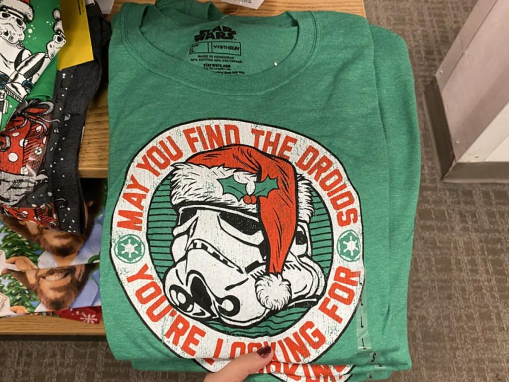hand holding folded Christmas tshirt