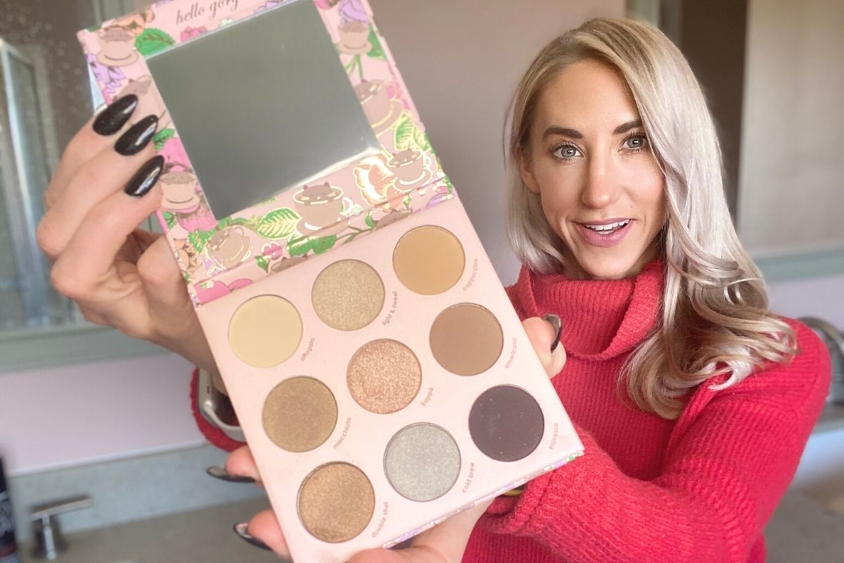 A woman holding a Winky Lux eyeshadow palette
