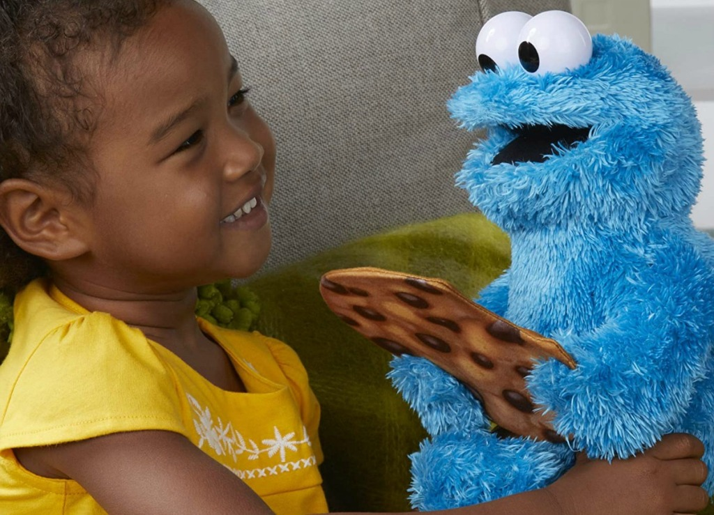 little girl holding cookie monster talking plush toy