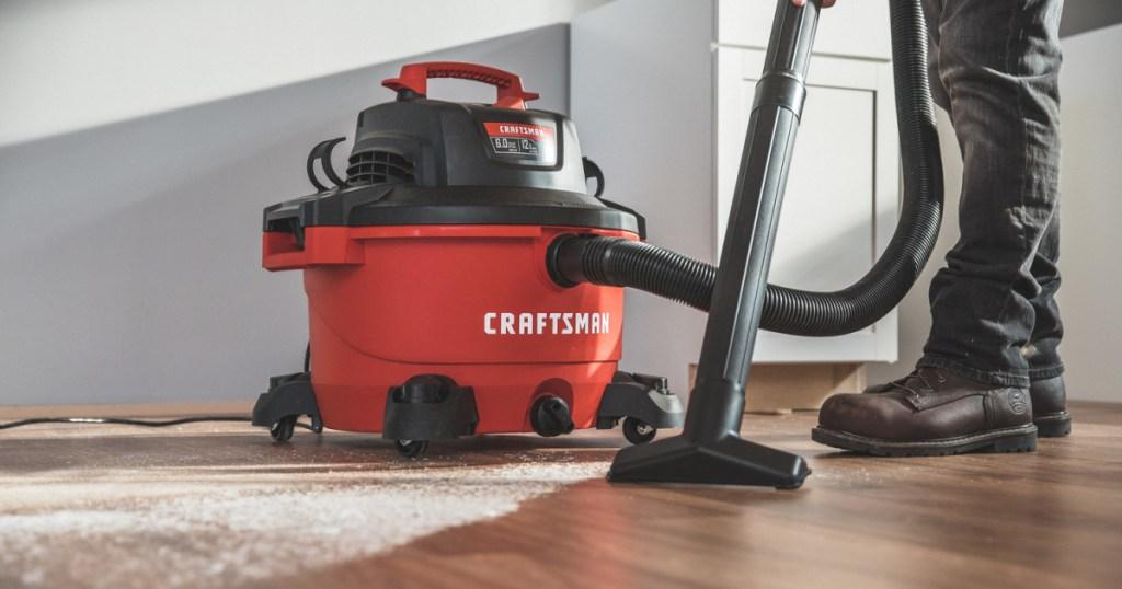 red wet/dry vacuum being used to clean up hardwood floor