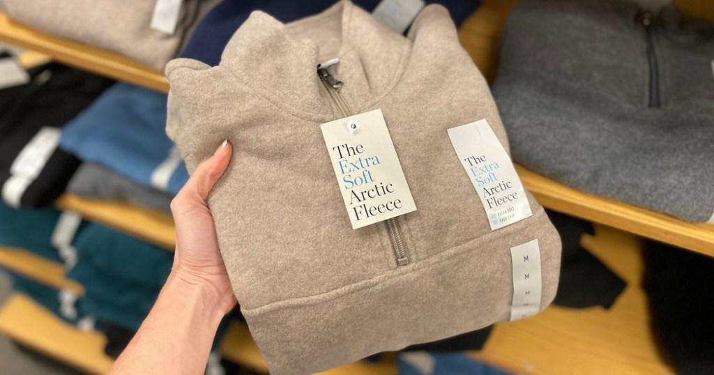 hand holding men's fleece shirt folded in store