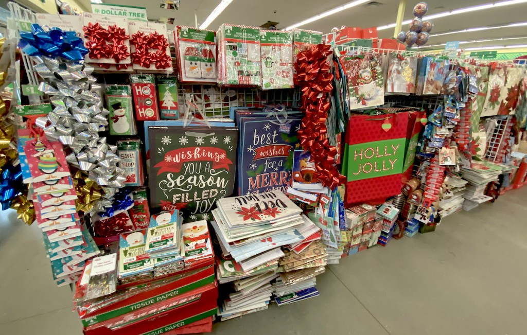 aisle of dollar tree christmas decorations bags hanging up with bows and tissue paper