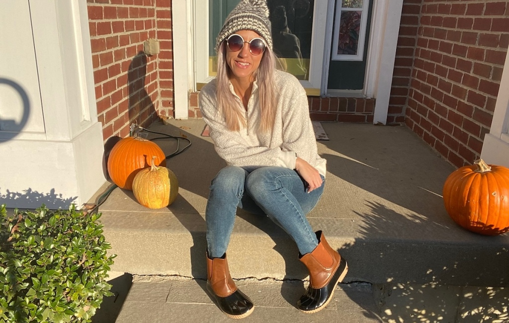 woman sitting on porch with pumpkins