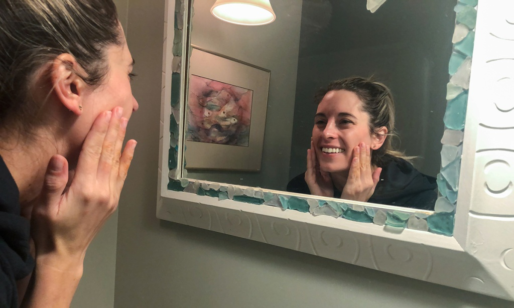 woman in mirror using skincare products