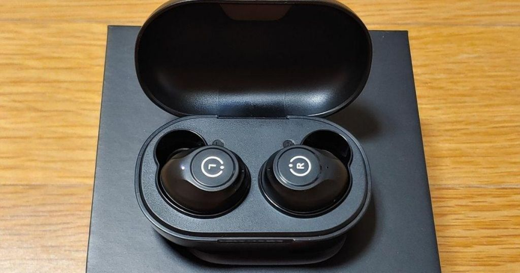 earbuds in a case sitting on a table