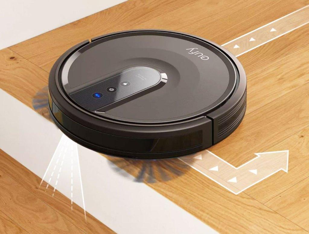 round black robotic vacuum cleaning hardwood floor near stairs