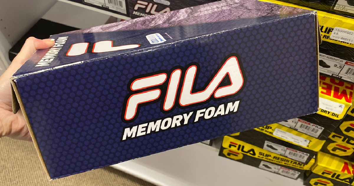 hand holding shoe box labeled FILA in store