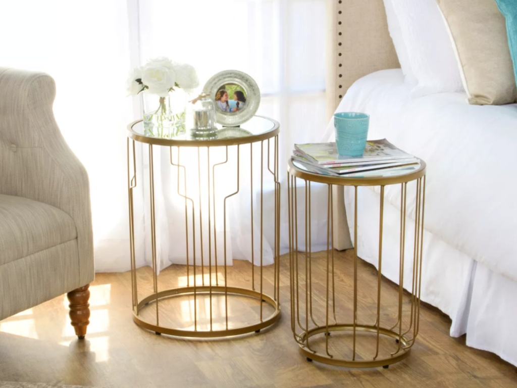 two gold nesting tables in between a chair and bed