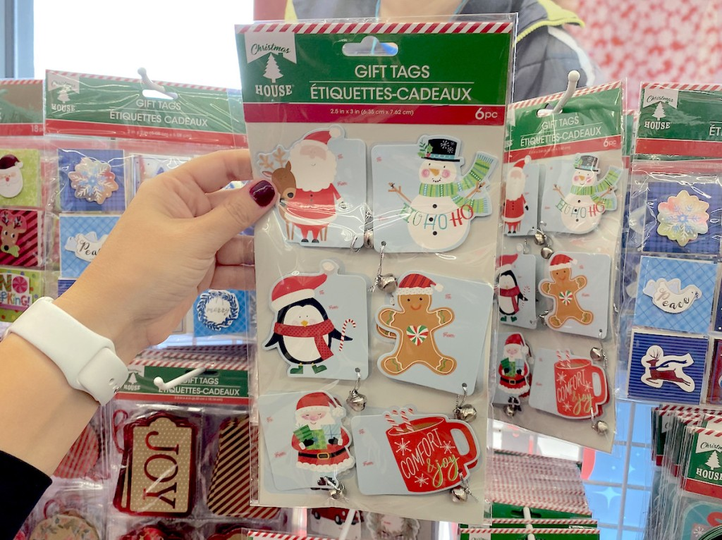 hand holding gift tags set in dollar tree christmas decorations aisle