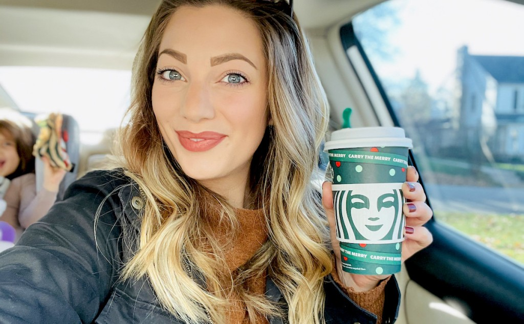 woman holding holiday starbucks cup in car