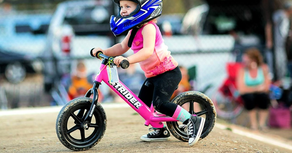 girl riding Strider 12 Balance Bike in pink with blue helmet
