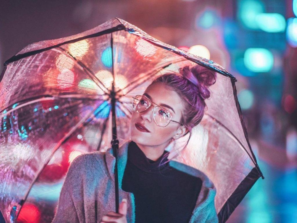 woman wearing glasses holding umbrella at night