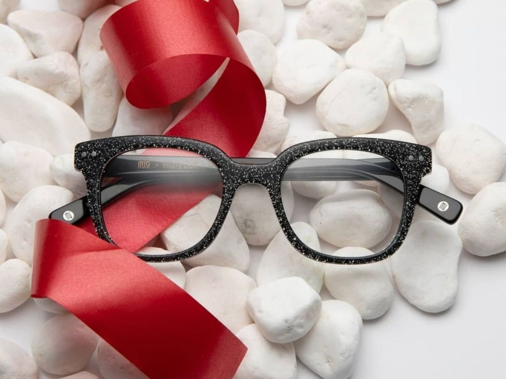 black glasses with white rocks and red ribbon