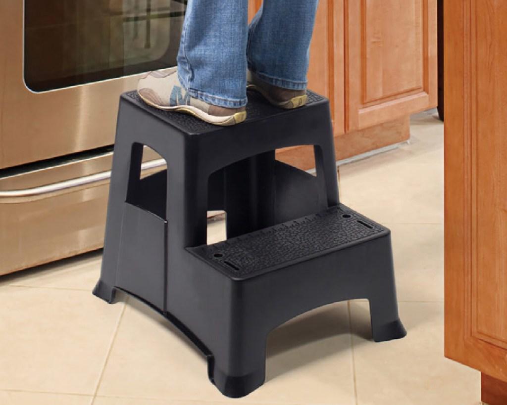 person standing on gorilla ladder plastic stool