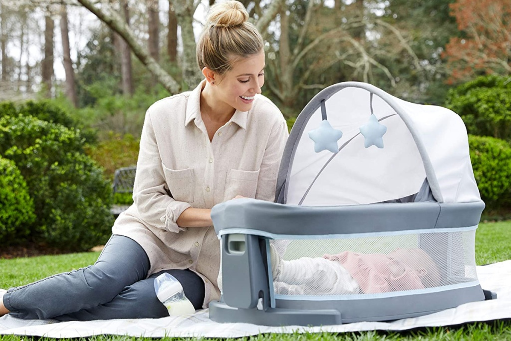 mom sitting next to baby in graco playard