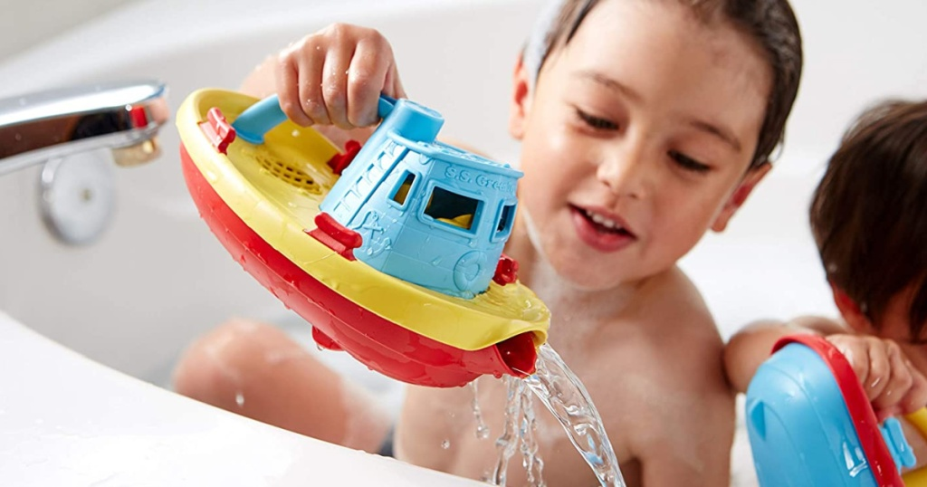 boy playing with green toys tug boat and submarine in tub