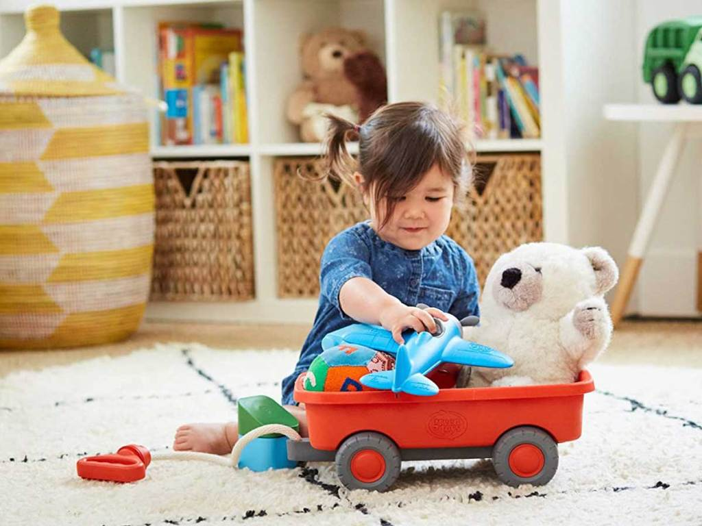 child playing with toys in a wagon