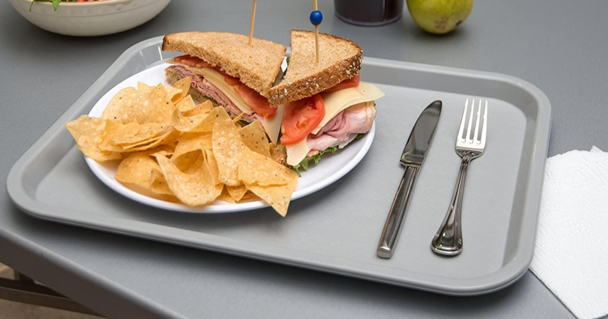 grey food tray with silverware on the right of a white plate holding a sandwich and chips