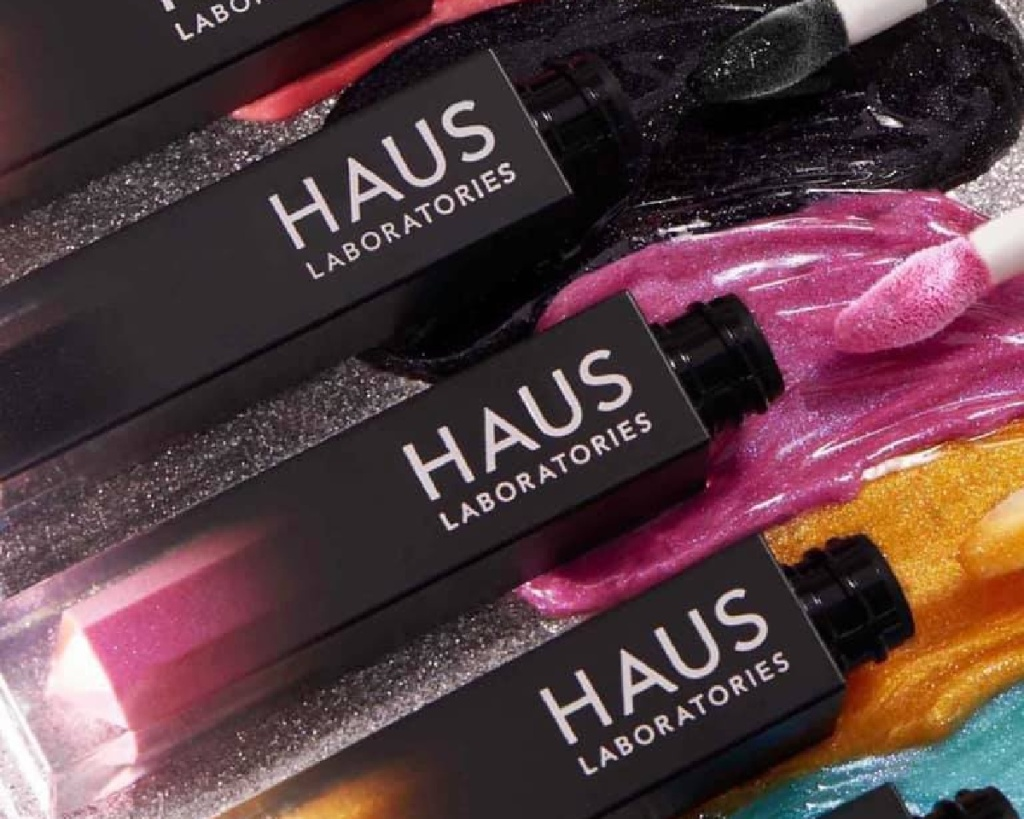 haus laboratories riot lipgloss in several shades opened and pouring out