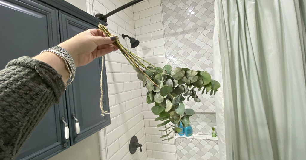 holding a bouquet of eucalyptus in the shower