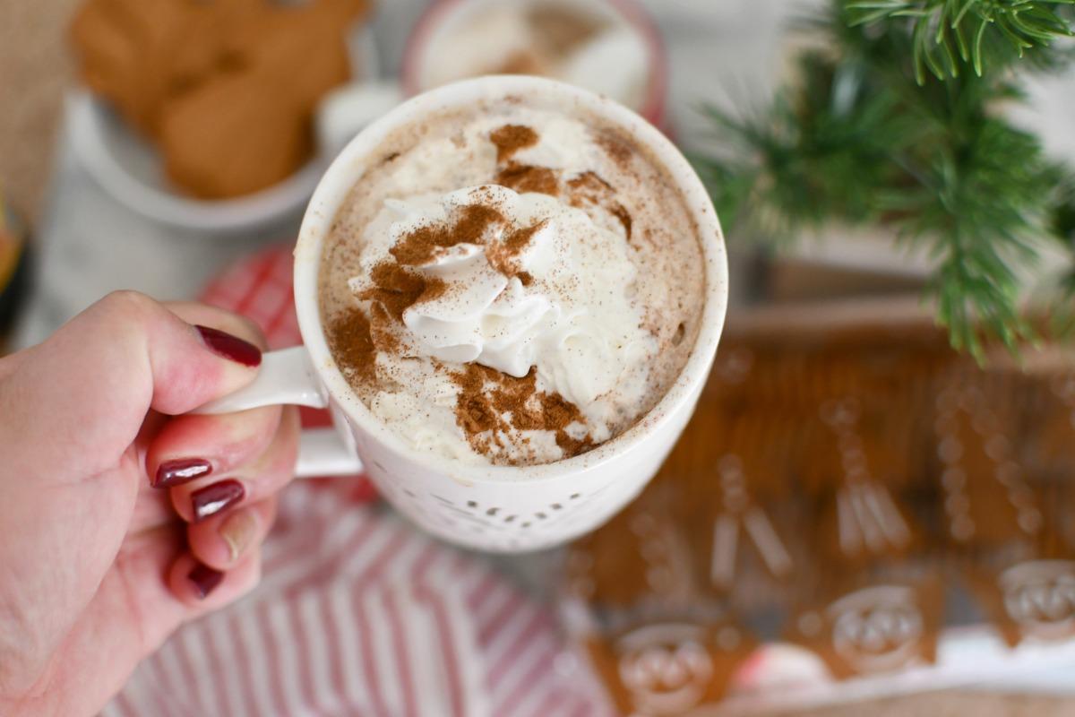 holding a Starbucks gingerbread latte in white mug