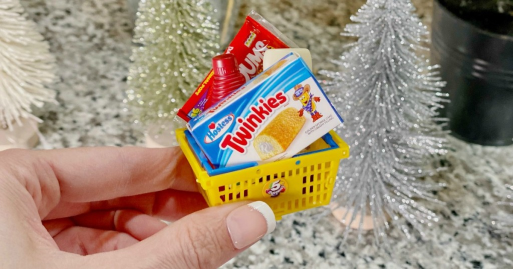 hand holding mini yellow grocery basket with miniature food brands
