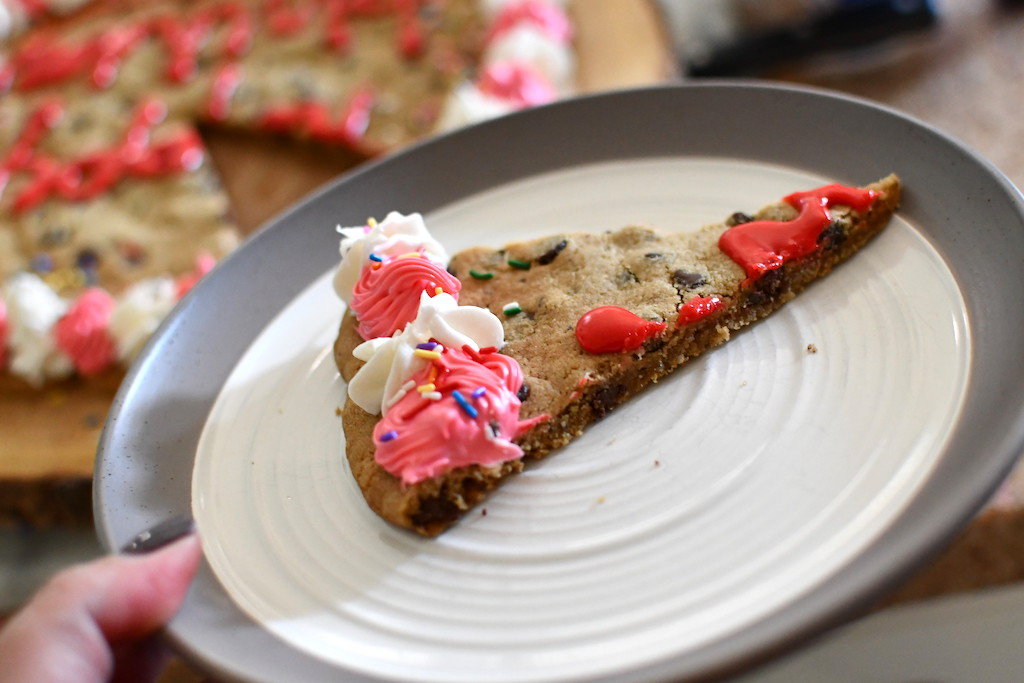 holding plate with slice of cookie cake
