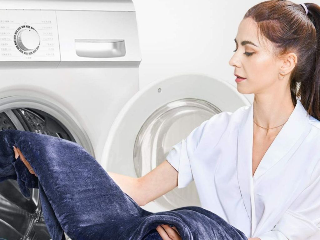 woman putting navy heating pad into washer