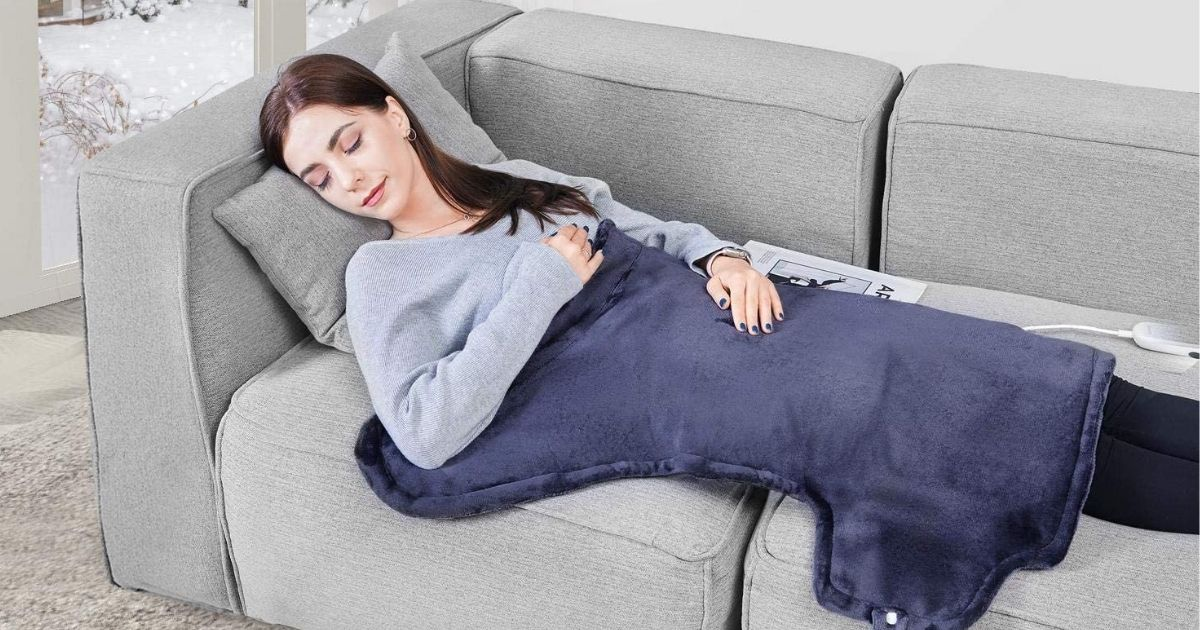 woman laying on couch with blue heating pad over her