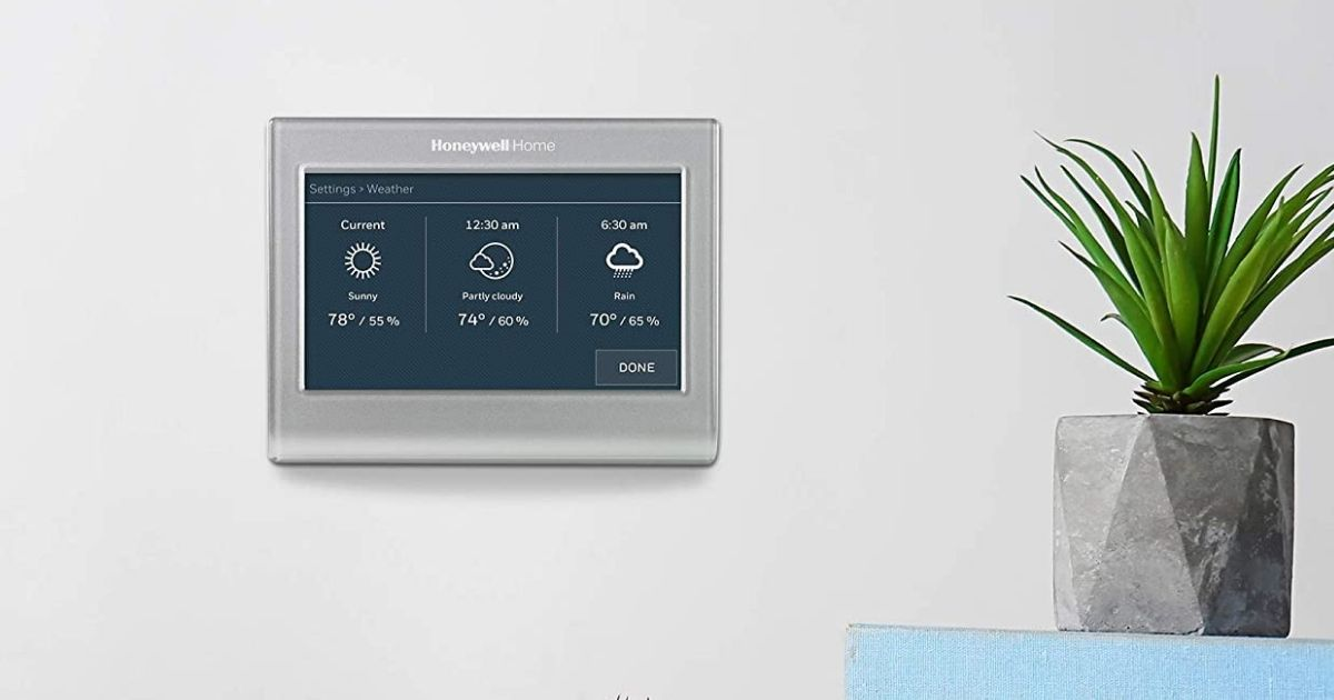 smart thermostat on wall next to plant