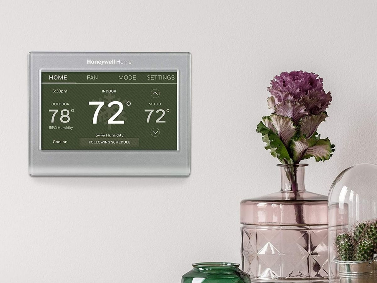 smart thermostat on wall next to flowers