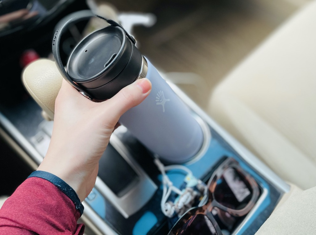 hand putting hydro flask bottle in cup holder