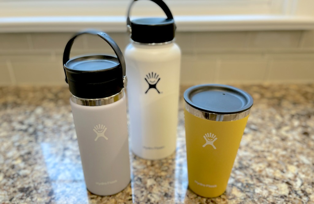 purple white and yellow hydro flask bottles on countertop
