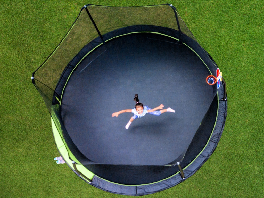 kid jumping on a Jump King 14ft Trampoline With Basketball Hoop