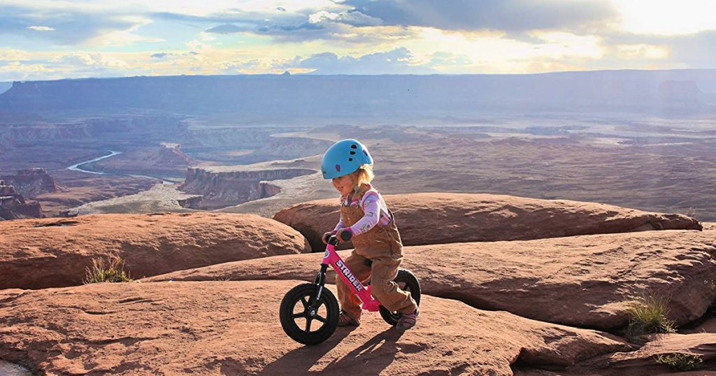 girl riding Strider 12 Balance Bike in pink