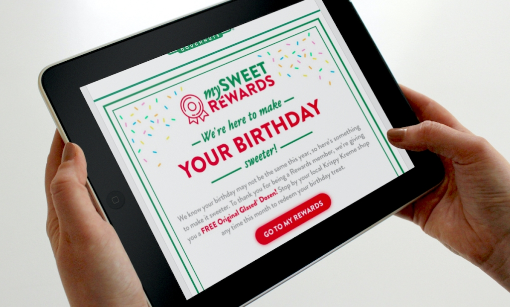 hand holding an ipad with krispy kreme birthday freebie dozen donuts