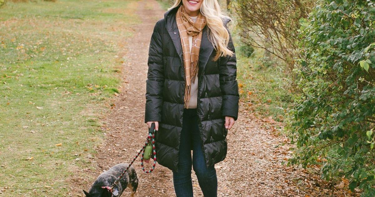 woman wearing black puff jacket walking her dog