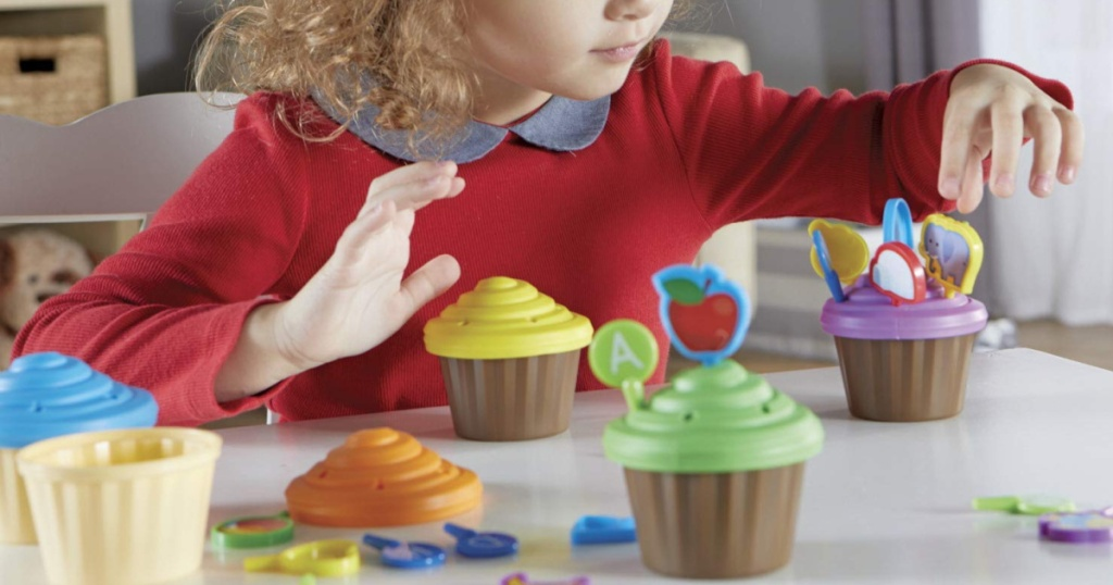 little girl playing with learning resources cupcake party toppers