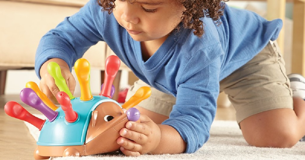 little boy playing with learning resources spike the hedgehog