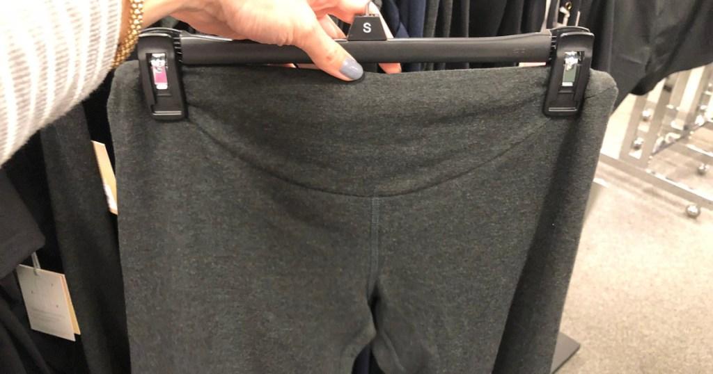 hand holding up leggings on hanger in store