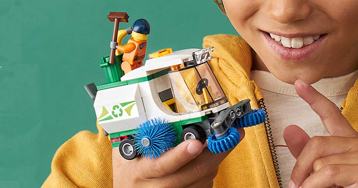 little boy holding a lego city sweeper