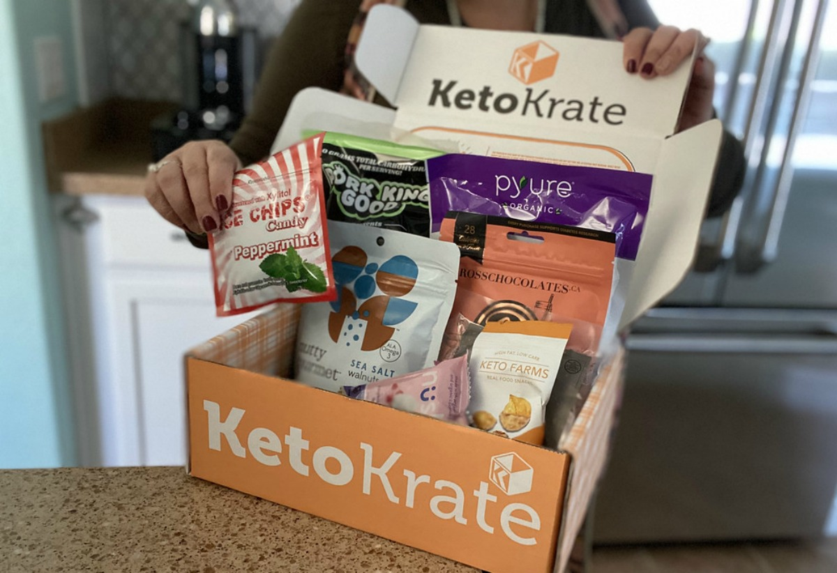 woman standing behind a keto krate box showing contents