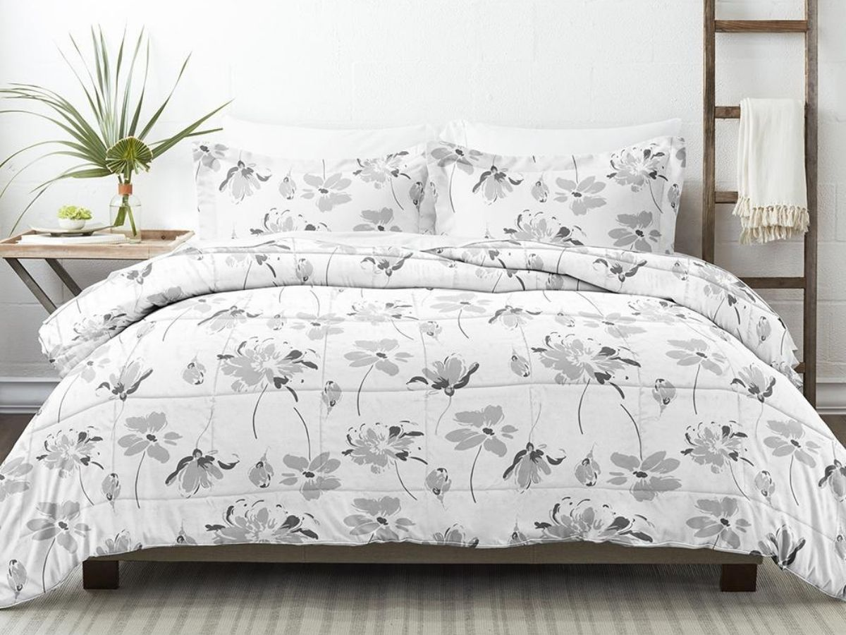 flowered gray and white comforter set on bed