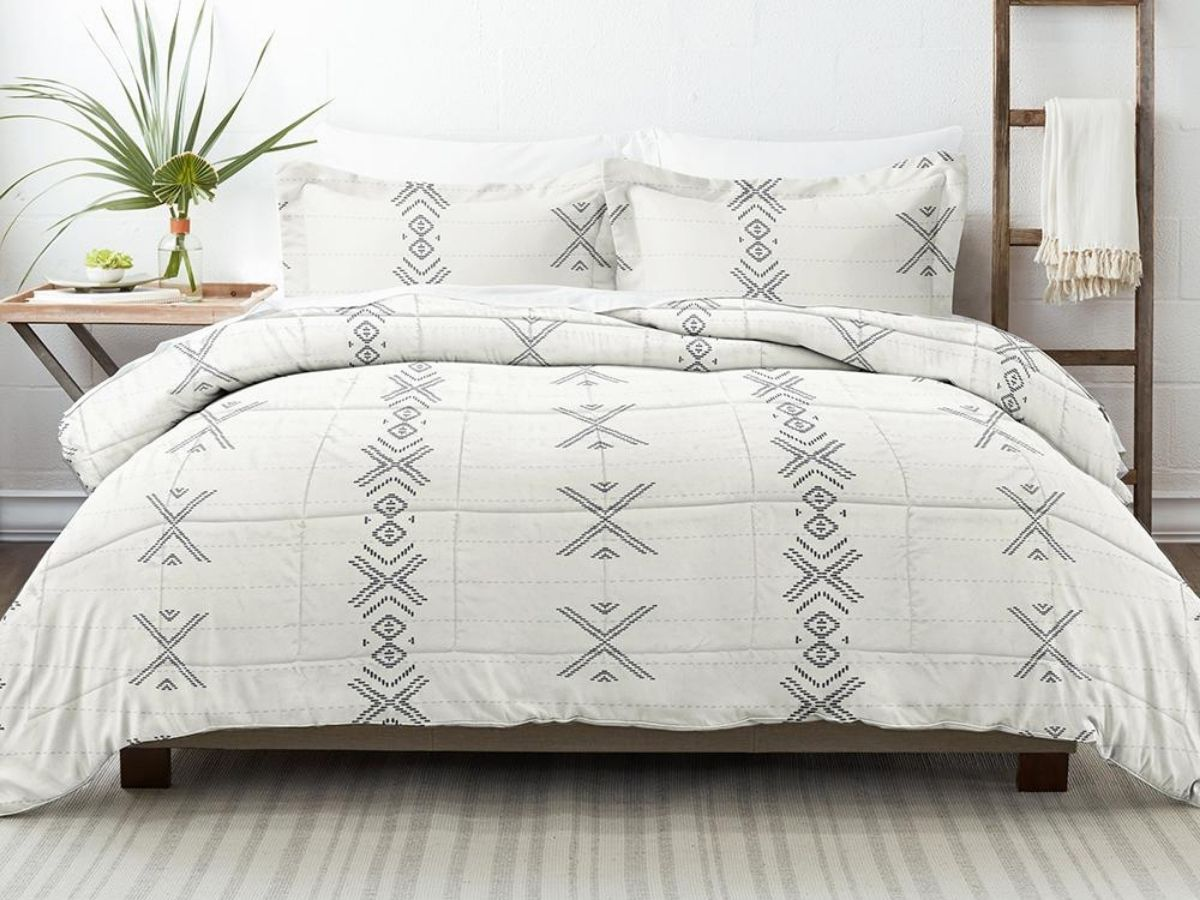gray and white stitched comforter on bed