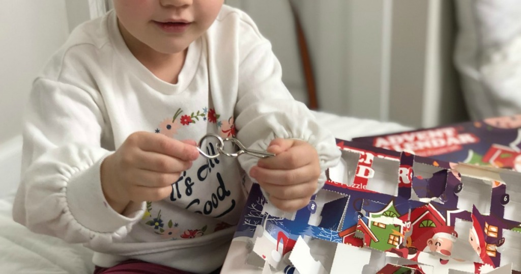 little girl playing with metal puzzle from Advent calendar