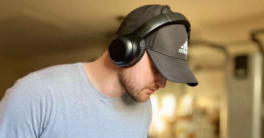 man wearing a baseball cap and headphones looking at the ground