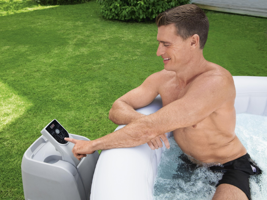 man in spa leaning out to push control panel