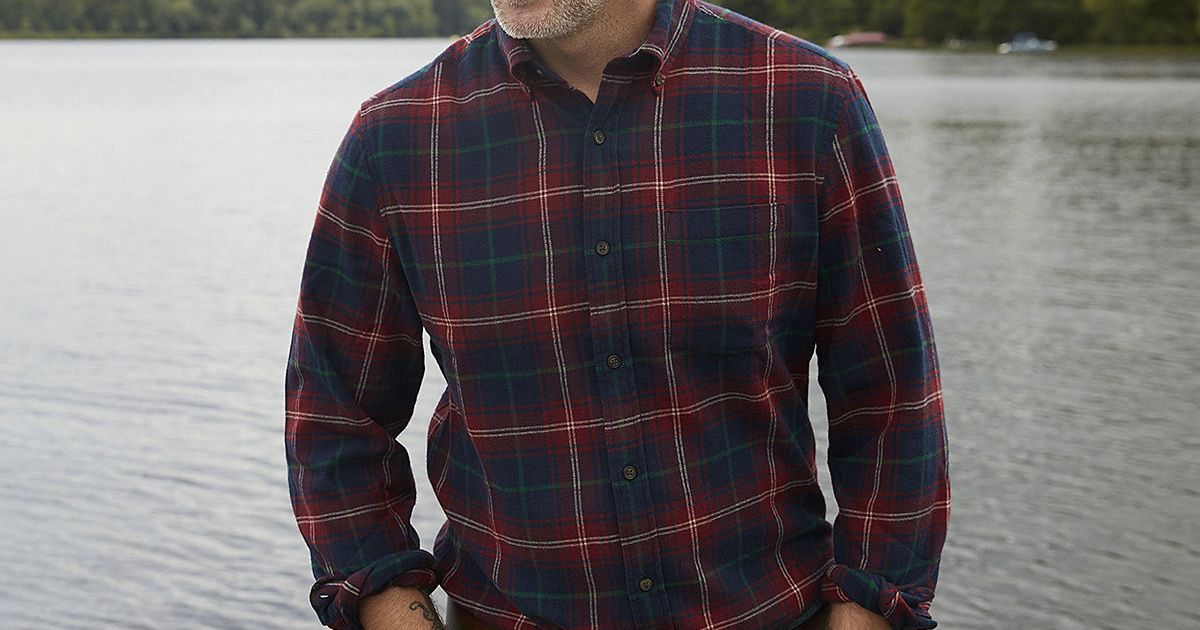 man wearing flannel shirt in front of lake