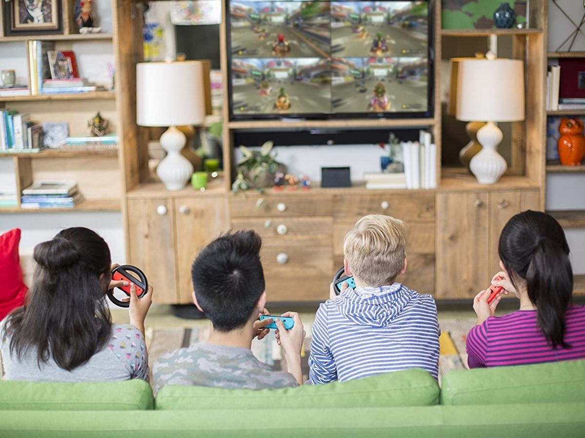 four kids sitting on green couch playing nintendo switch video game