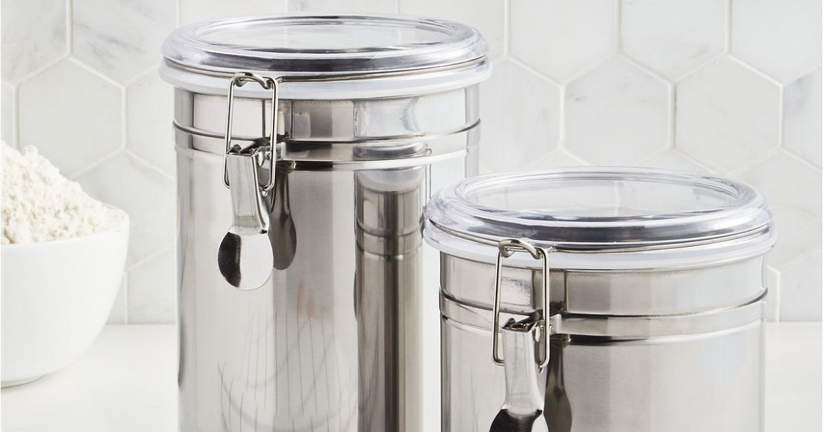 stainless steel canisters on counter top with white bowl of popcorn in background